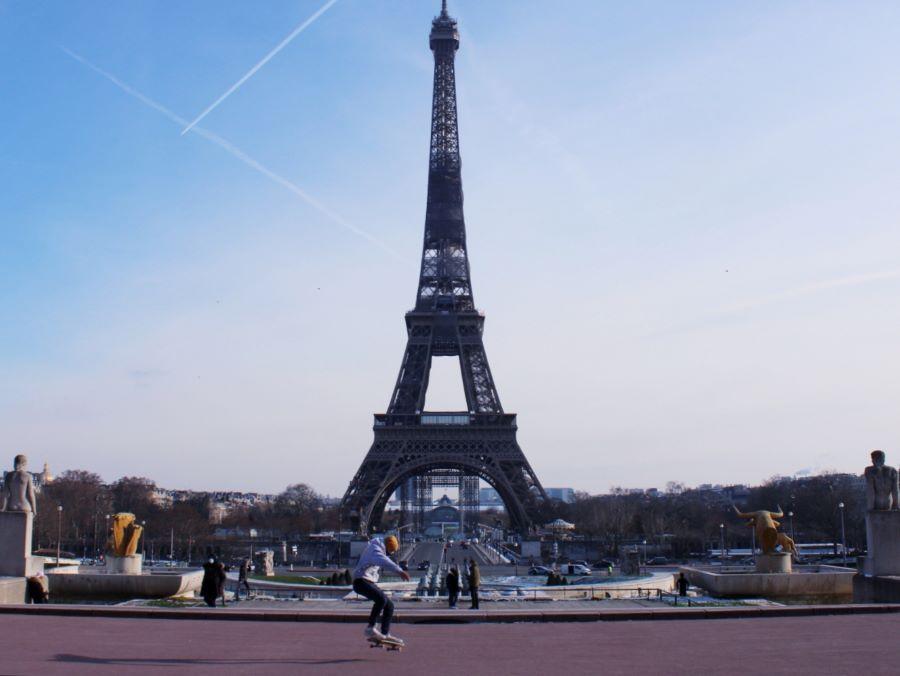 Un skateur réalise un ollie devant la tour Eiffel vu depuis le Trocadéro